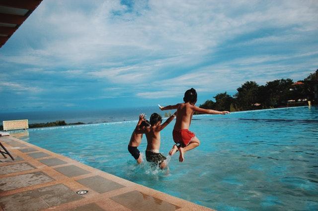 děti skáčou do bazénu
